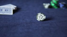 Black poker chip spinning slowly. On the gaming table stock footage