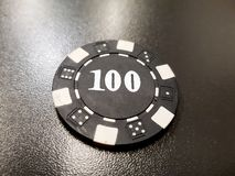 A black poker chip of 100 on a black table. Chance vegas win gamble finance risk background plastic leisure fortune luck casino entertainment bet game hazard stock photo