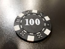 A black poker chip of 100 on a black table. Chance vegas win gamble finance risk background plastic leisure fortune luck casino entertainment bet game hazard stock image
