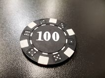 A black poker chip of 100 on a black table. Chance vegas win gamble finance risk background plastic leisure fortune luck casino entertainment bet game hazard stock images