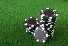 Black poker chips. Some black poker chips on green table Stock Photography