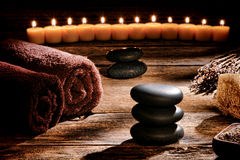 Black Polished Massage Stones Cairn in Rustic Spa. Black polished smooth hot massage stones in a Zen inspired cairn on a vintage wood boards table in a rustic royalty free stock photo
