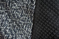Black polyester and grey tweed sewn together. Black polyester and grey tweed fabric sewn together Royalty Free Stock Image