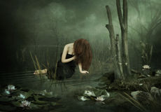 The black pond. The young girl in black dress, with long hair his head bowed down on the pond with lilies Stock Photography