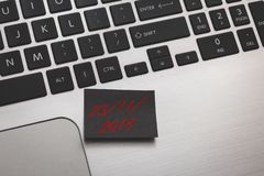 Black note with marketing message of Black Friday sale on silver laptop. Black post it with marketing message of Black Friday sale on silver laptop royalty free stock photography
