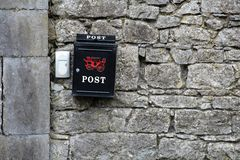 Black Postbox on a stone wall. Black Postbox with white text on a stone wall Stock Images
