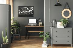 Black poster on grey wall above desk with mockup in home office interior with mirror. Real photo. Concept stock photography