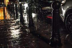 Black Posts on Black Pavement Beneath Falling Rain Stock Photos