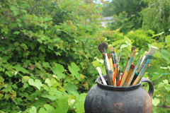 Black pot with brushes in green leaves. Old pot with paint brushes in green grape leaves Stock Photo