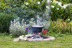 Black pot in garden camp fire. Black pot outside in a garden to cook a meal in camp fire for a party Stock Image