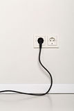 Black power cord cable plugged into european wall outlet on whit Royalty Free Stock Photo