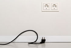Black power cord cable unplugged with european wall outlet on wh Royalty Free Stock Photo