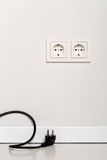 Black power cord cable unplugged with european wall outlet on wh Royalty Free Stock Image
