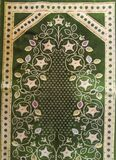 The Green prayer rug is a device made of cloth that usually has an Islamic image and style. Prayers are used by Muslims to keep