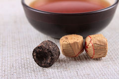 The black pressed Chinese tea on a linen napkin Royalty Free Stock Images