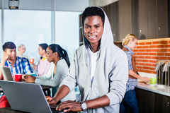 Black programmer in lounge of IT start-up. Coding software on his laptop, colleagues in the background Royalty Free Stock Photography