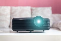Black projector on a table. Home movie theatre concept background stock photo