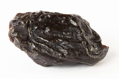 Black prunes. One black prune isolated on white stock images