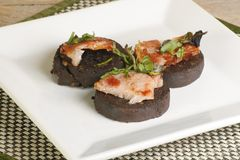 Black pudding. Three pieced of grilled black pudding bacon and garnish Stock Images