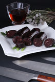 Black pudding in a white plate with glass of wine on dark table stock image