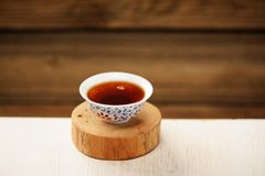 Black puerh tea in white bowl on wooden stand Royalty Free Stock Photos