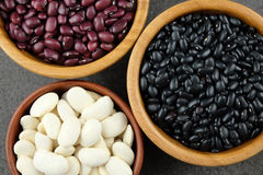 Black, purple and white dried beans in wooden bowls on a dark ru stock photo
