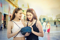 Black purse. Girls looking inside a black purse Royalty Free Stock Image