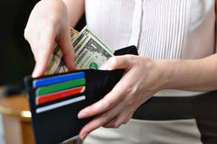 Black purse with money in woman`s hand Royalty Free Stock Photo