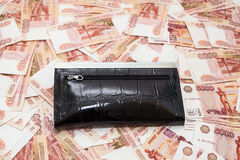 Black purse on scattered five thousandth banknotes of rubles Royalty Free Stock Images