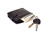 Black purse stuffed with money and car keys. Black purse stuffed with paper money and car keys isolated on white background royalty free stock photos
