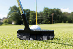 Black putter lines up a putt on the green. Close up view of a golf putting club with a white golf ball in front of it lining up a put toward the yellow flag pin Stock Photos