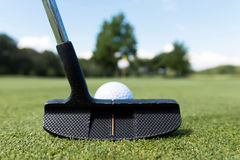 Black putter with white ball on the green. A black putter lines up a putt with a white ball on the green at a golf course Stock Image