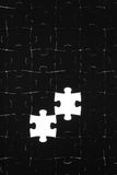 Black puzzle on a white background. Black puzzle laid out on a white background Royalty Free Stock Photo