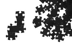 Black puzzle on a white background. Black puzzle laid out on a white background Stock Image