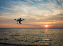 Black Quadcopter Drone Flying on the Sea Shore Under Blue and White Sky during Sun Set Stock Image