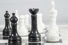 The black queen checkmates. Marble chessboard Stock Photography