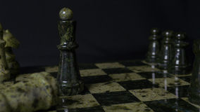 Black Queen in chess defeats white rock. Chess the queen wins victory over the game. Detail of chess piece on black. Background. Selective foucs 4K Stock Photo