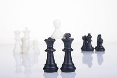 Black queen and king hold a white pawn Stock Photo