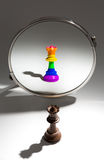 A black queen is looking in a mirror to see herself as queen covered with a rainbow flag. A black queen chess piece is looking in a mirror and sees herself as a Royalty Free Stock Photo