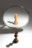 A black queen is looking in a mirror to see herself as a white queen. A black queen chess piece stands in front of a mirror. The reflection in the mirror shows Stock Photos