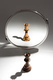 A black queen is looking in a mirror to see herself a an black and white colored queen. A black queen chess piece is looking in a mirror and sees herself  as a Royalty Free Stock Photography