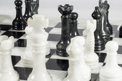 Black queen makes suicide check. Queen's gambit. Marble chessboard Stock Image