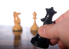 Black queen moved on chessboard. Chess piece moved by hand on a chessboard as a business concept Royalty Free Stock Images