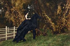 Black queen witch horseback on a black horse in a gloomy forest Stock Photo