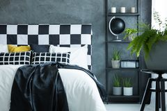 Black quilt on bed. Plant in blue pot on stool in dark bedroom with black quilt and pattern pillows on bed stock photography