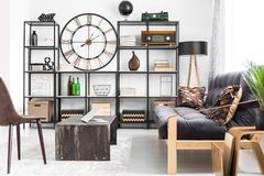 Black rack with decorations. Black metal rack with books, vintage radio and decorations standing in man apartment interior Stock Photos