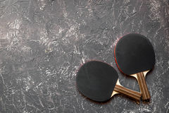 Black racket for ping pong ball gray background top view Stock Photography