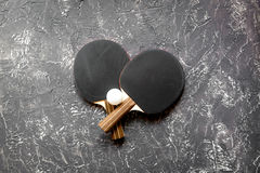 Black racket for ping pong ball gray background top view Royalty Free Stock Image