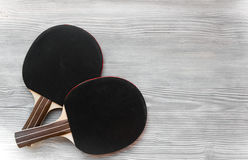 Black racket for ping pong ball wooden background top view Stock Images