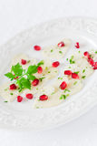 Black radish carpaccio. Heart-shaped with pomegranate seeds and parsley on plate, selective focus Stock Photo